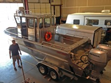 """CRITFC Fish Biologist John Whiteaker next to CRITFC's new research vessel. To give an idea of the size of the boat, Whiteaker is 6' 5""""."""